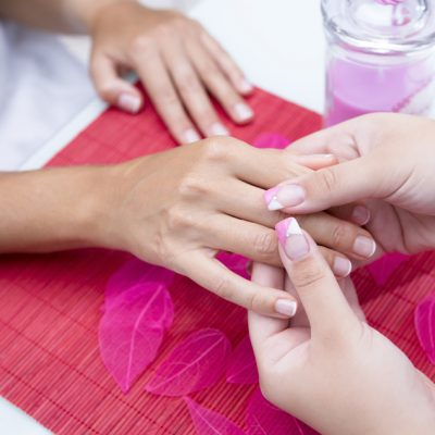 closeup of the hands of a young woman receiving a hand massage by a beautician on a beauty session at the nail salon - focus on the thumbs of the beautician